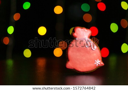 gingerbread cookie of red bag Santa's with gifts over defocused colored lights of garland. Traditional Christmas food. Christmas and New Year holiday concept #1572764842
