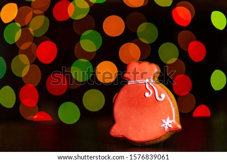gingerbread cookie of red bag Santa's with gifts over defocused colored lights of garland. Traditional Christmas food. Christmas and New Year holiday concept #1576839061