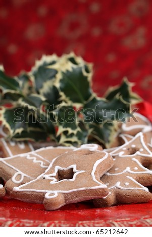 Gingerbread cookies and holly twig on Christmas background. Shallow dof