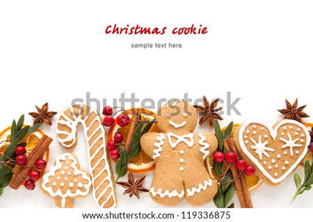 Gingerbread cookies and spices over white background close up