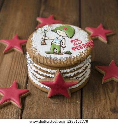 Gingerbread cookies casket with decor on 23 february holiday - Red stars cookie, little soldier with a gun, the inscription in Russian February 23 - on wooden background. Close up, Selective focus #1288158778