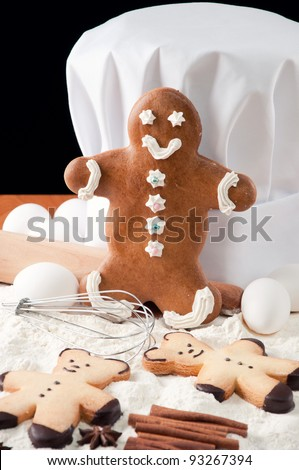 Gingerbread cookies, chef's hat and food ingredients on a kitchen table, black background