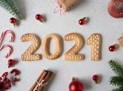 Gingerbread cookies in the form of numbers, gingerbread New Year 2021 and festive decor on grey background . Top view. Flat lay
