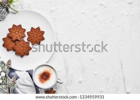 Gingerbread cookies with hot cocoa drink or eggnog on white marble table covered with snow. Top view of traditional Christmas gingerbread cookies with copy space.