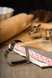 Gingerbread cutters and Christmas linen next to rolling pin on wooden table with baking mold,  spruce cones and brown paper on background. Vertical. Christmas card.
