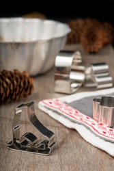 Gingerbread cutters and Christmas linen on wooden table with baking mold and  spruce cones on background. Vertical. Christmas card. Heart shape gingerbread cutter in front.