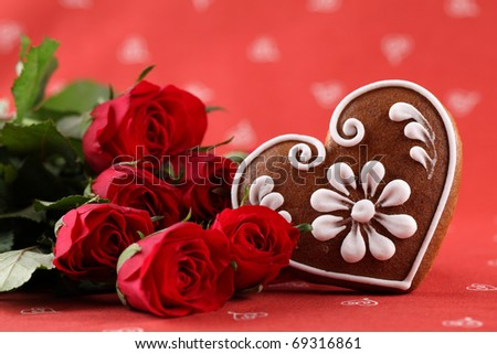Gingerbread heart and red roses on red background. Shallow dof