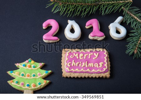 Gingerbread homemade cookies with icing and christmas tree branch on a black table or board for background. Figures 2016 New year theme. #349569851