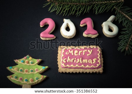 Gingerbread homemade cookies with icing and christmas tree branch on a black table or board for background. Figures 2016 New year theme. Toned. #351386552