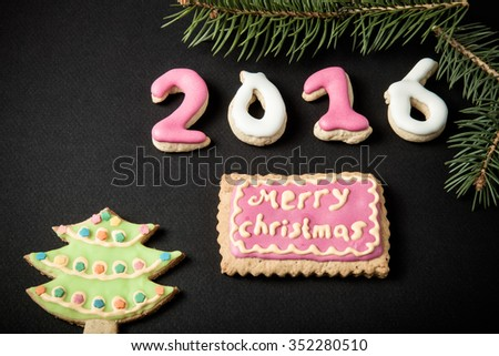 Gingerbread homemade cookies with icing and christmas tree branch on a black table or board for background. Figures 2016 New year theme. Toned. #352280510
