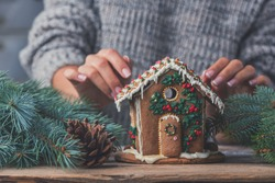 Gingerbread house and women's hands in sweater, the concept of preparation for the Christmas holidays