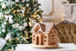 Gingerbread house, concept holiday of Christmas and Happy new year. Defocused lights of Christmas tree. Morning in the bright living room. Holiday mood.