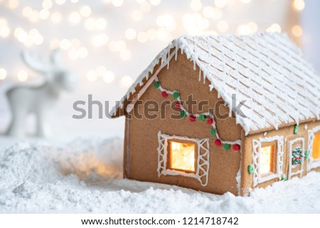 Gingerbread house in snow with twinkling silver light background