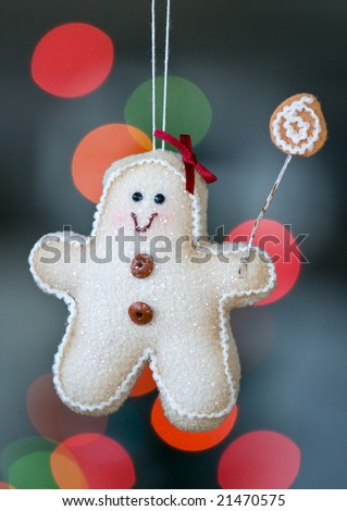 Gingerbread man decoration hangs from a christmas tree