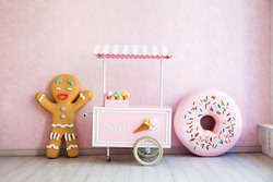 Gingerbread man, donut and ice-cream handcart in funny room interior