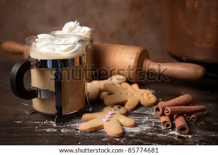 Gingerbread men cookie biscuits with hot coffee and whipped cream