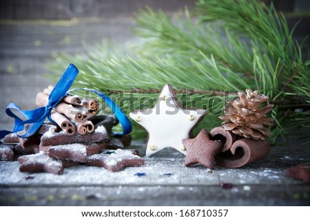 Gingerbread star cookies and cinnamon sticks decorated for Christmas on wooden background.