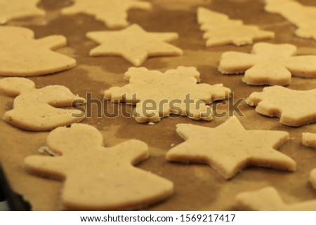 Gingerbread Stars and snowmans on sheet metal are ready to oven. Christmas holidays are here after year´s pause. Parents and children do some special sweets for great time. Concept of family and smile #1569217417