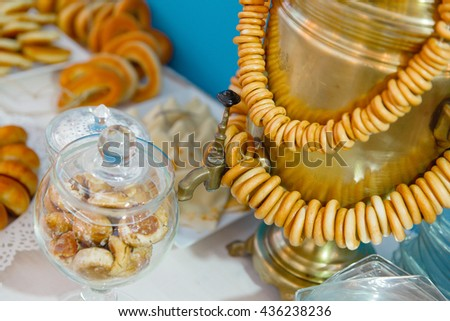 Gingerbreads in a glass bowl stand on the table behind a samovar