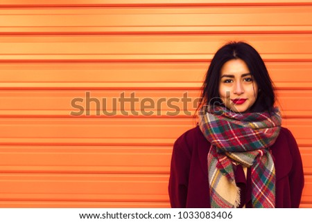 Girl a little disheveled by the wind, dressed in a red coat and a scarf of colors, in front of an orange shutter.