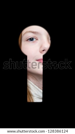 Girl a teenager spies in a keyhole