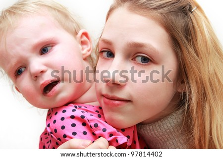 Girl - a teenager with a year-old child in her arms - stock photo