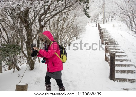 Girl accidentally tourists taking pictures of flowers and trees on beppu ropeway was covered with snow after a blizzard struck hard.