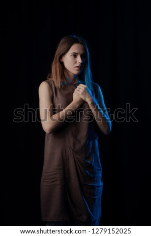 Girl Actress on stage plays emotions in blue theatrical light #1279152025