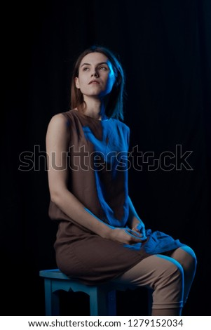 Girl Actress on stage plays emotions in blue theatrical light #1279152034