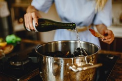 Girl adding white wine to a pan with mussels, woman preparing food