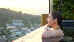girl admires pictorial blurry hilly landscape and small buildings sitting in hotel swimming pool in summer evening closeup