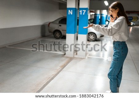 Girl after shopping discovered the loss of her automobile. Angry woman talking about missing car on phone. Vehicle theft concept Foto stock ©