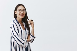 Girl ahieved everything with own strength. Portrait of carefree and happy attractive woman in glasses and striped blouse, playing with hair strand and smiling broadly with confidence at camera