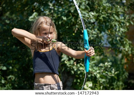 Girl aim with bow on background of nature