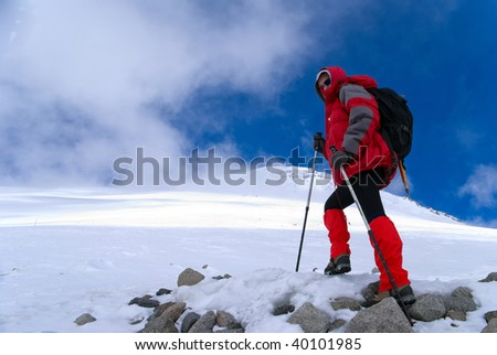 Girl - an mountaineer in red jacket walks up the top of mountain
