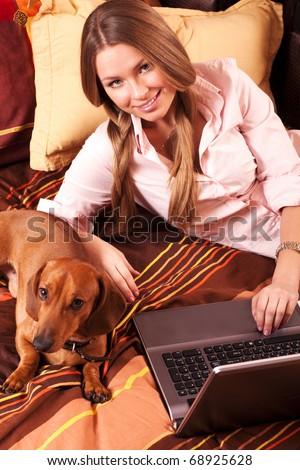 girl and a computer at home and dachshund
