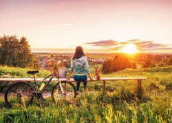 Girl and a dog are looking at a beautiful sunset on the horizon. Walking with a dog on a bike in the evening. Young girl and a dwarf chihuahua look at the setting sun in the evening. People at sunset