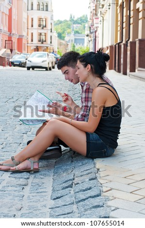 Girl and a guy sitting on street with map during the tourist walk.