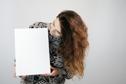 Girl and blank canvas. Copy space on canvas board for image or message. Young woman looking at mockup poster and standing over grey background.