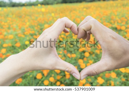 Girl and boy hands in heart form love with flowers. #537901009