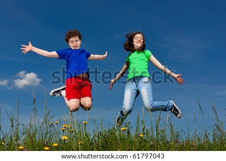 Girl and boy jumping, running against blue sky
