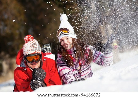Girl and boy laying on the snow in park