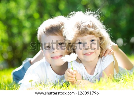 Girl and boy lying on green grass in spring park