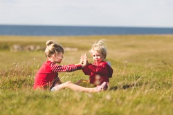 girl and boy playing together outdoors. small brother having fun with older sister. siblings spending time in the park.