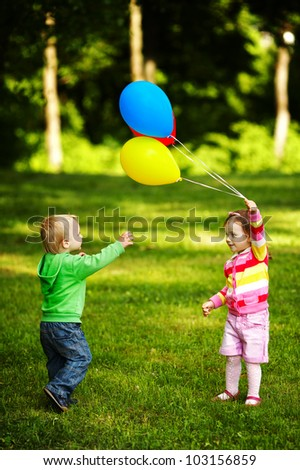 girl and boy playing with balloons in park