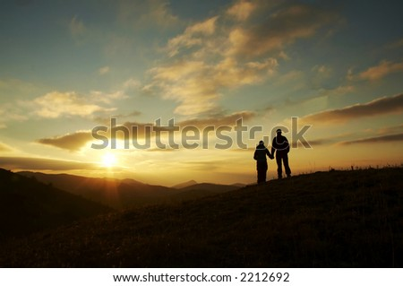Girl and boy silhouette on the sunset background