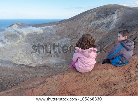Girl and boy sitting on the rim of volcano crater of Vulcano island near Sicily, Italy