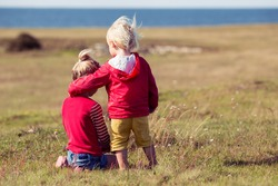 girl and boy together outdoors. small brother embracing older sister. siblings preschooler playing in park.