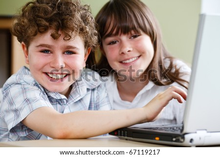 Girl and boy using computer at home
