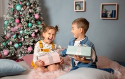 Girl and boy with gifts under the Christmas tree. Children laugh. Children are happy. A girl and a boy are happy with new year's gifts.